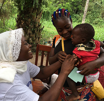 Annie Ayoko (left) cheers up a baby to whom she has just subministrated a vaccine. © T. Baldassarri Höger von Högersthal / Interholco. All rights reserved.